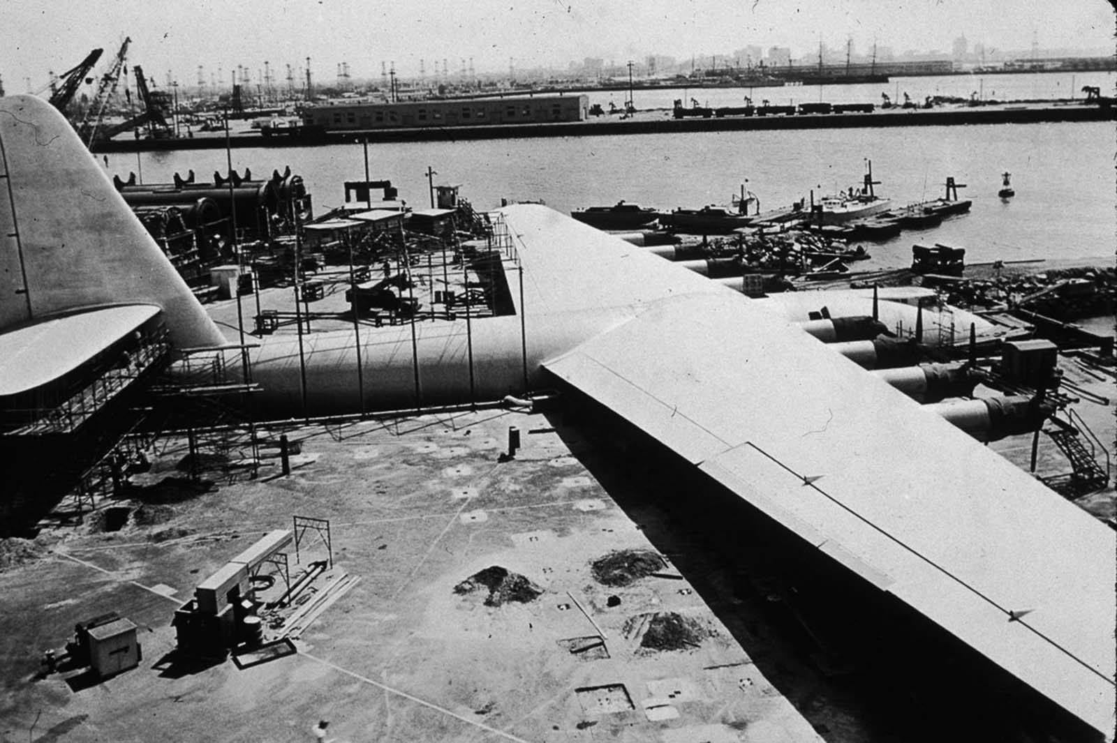 A house moving company transported the airplane on streets to Pier E in Long Beach, California. They moved it in three large sections: the fuselage, each wing—and a fourth, smaller shipment with tail assembly parts and other smaller assemblies.