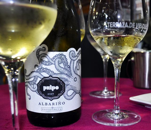 la etiqueta tiene dibujado un pulpo y sus tentáculos sobresalen de lo que seria el rectángulo tradicional de las etiquetas del vino, junto dos copas con vino