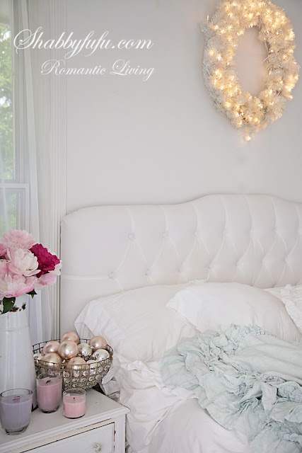 romantic decorating looks for Christmas - a romantic bedside upholstered headboard and pink flower arrangement