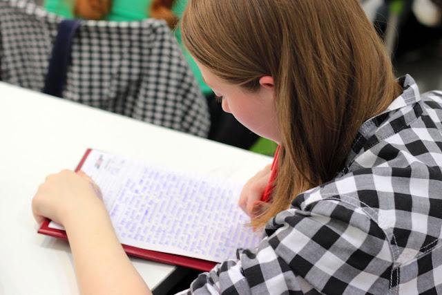 Chica escribiendo en una clase