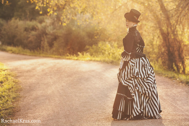 Woman dressed in black and white striped victorian bustle skirt with top hat