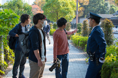 Trumpwatchers talk to a policeman in front of the Geihinkan