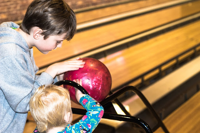 An older child helping a younger child position the bowling ball and enjoy the party
