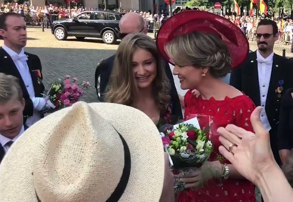 Crown Princess Elisabeth is wearing black floral print wrap midi dress. Queen Mathilde wore a red lace dress by Natan. Princess Eleonore