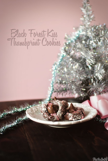 Three Black Forest Thumbprint Cookies on a white plate with a silver Christmas tree in the background