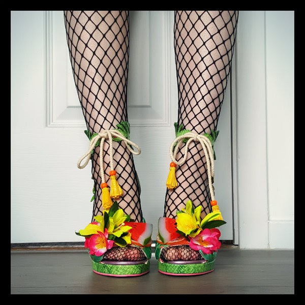 legs face on wearing bright flower and fruit open toed shoes with yellow grass skirt trim and rope ankle ties