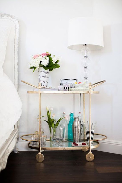 A gold bar cart makes a charming and creative bedside table