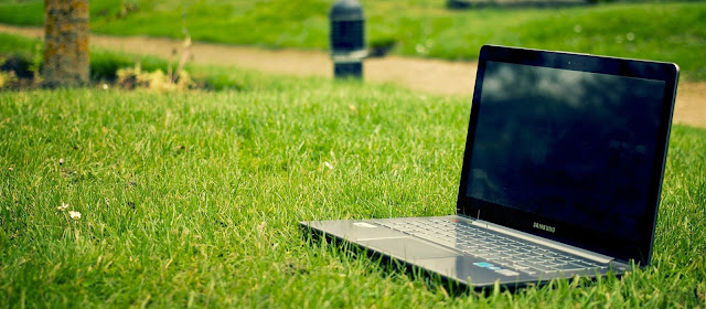 a laptop lies in grass at a park