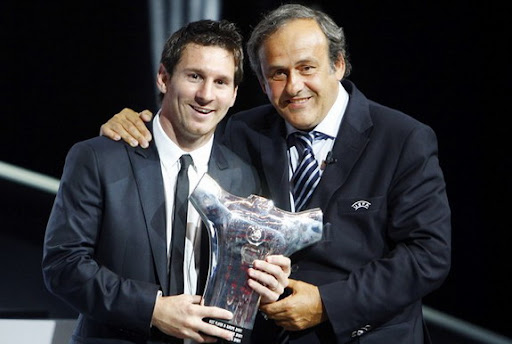 Lionel Messi poses UEFA president Michel Platini afyer receiving the trophy of Best player in Europe