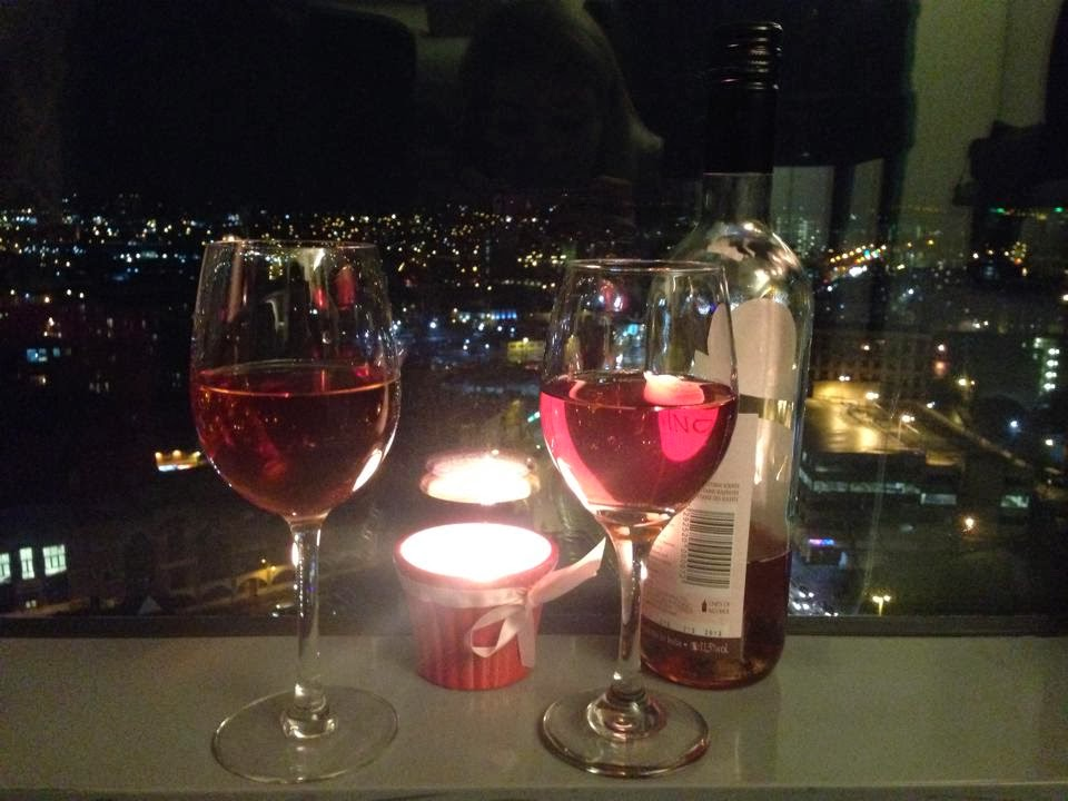 two full wine glasses on the window still with a candle burning behind them and a bottom of rose to the side