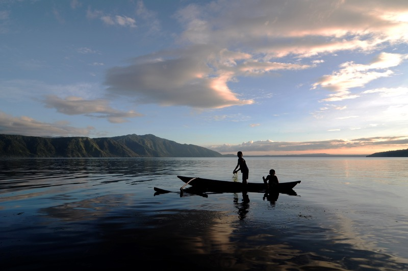 Anak-anak sedang berada di atas perahu untuk mencari ikan di Danau Ranau