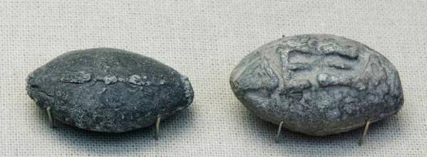 Proyectiles de honda de la antigua Grecia con inscripciones. En una de las caras aparece un rayo alado, y en la otra, escrito en griego, «chúpate esa», en relieve.