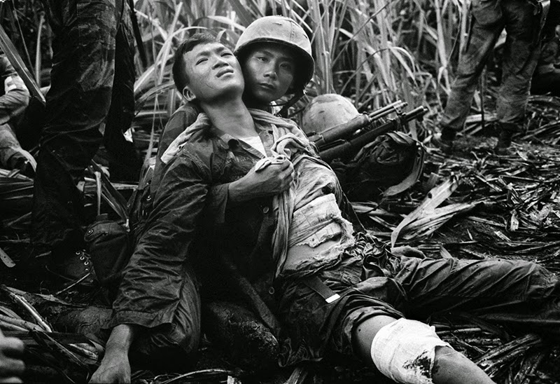 A south vietnamese marine severely wounded in a viet cong ambush is comforted by a comrade in a sugar cane field at duc hoa about 12 miles from saigon