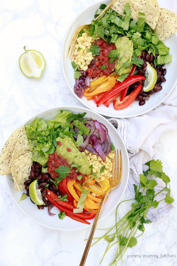 Beautiful vegan fajita quinoa bowls with salsa and guacamole.