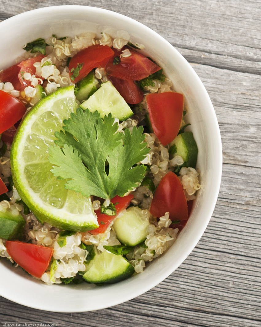 Quinoa with lime, tomato and parsley in a white bowl arranged as a flatlay on barnboard