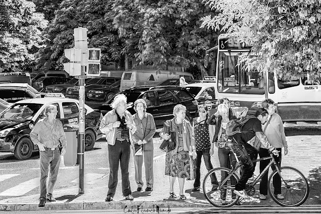Un ciclista pasa frente a gente en fila en semáforo.