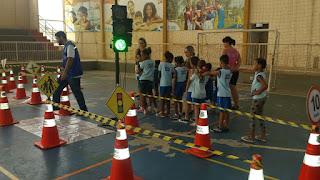 Crianças participando de circuito de Educação para o Trânsito, com cones e semáforo.
