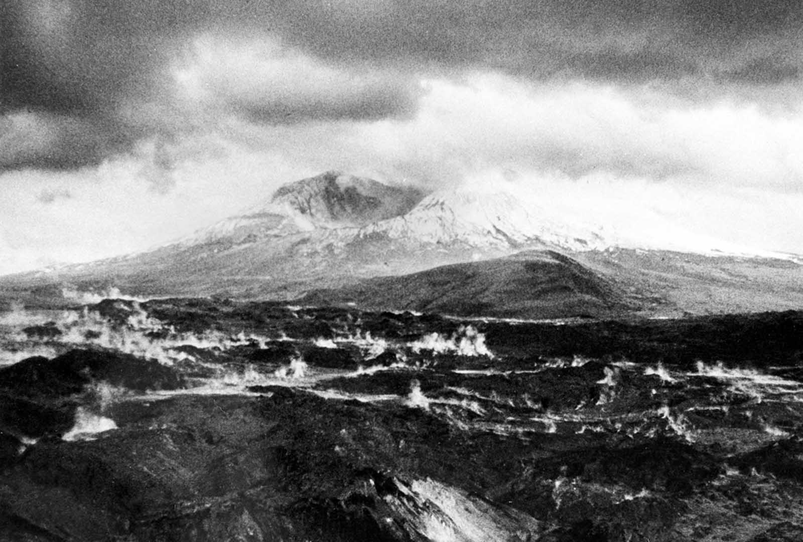The crater left at the summit of Mt. St. Helens, after it lost more than 1,300 feet of elevation to the catastrophic landslide and eruption of May 18, 1980, the surrounding landscape still steaming.