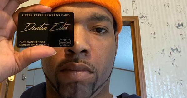 Black man holding metal Mastercard debit card