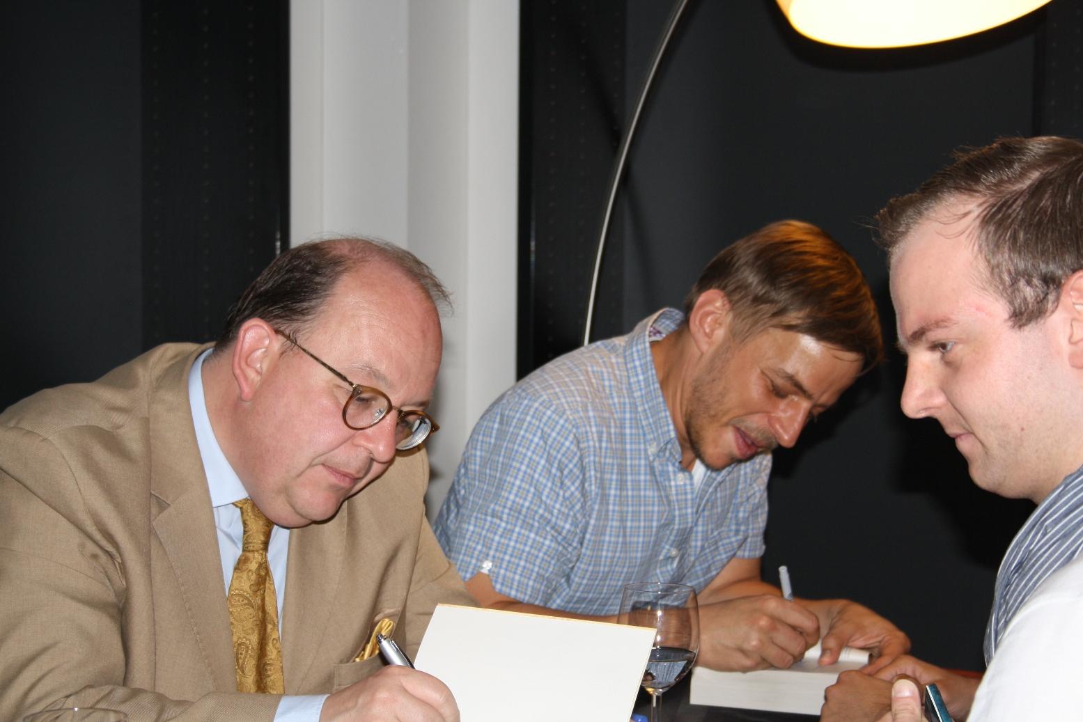 Denis Scheck und Tom Wlaschiha signieren Bücher