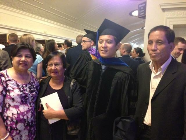 Family taking a photo with a recent graduate in graduation garb