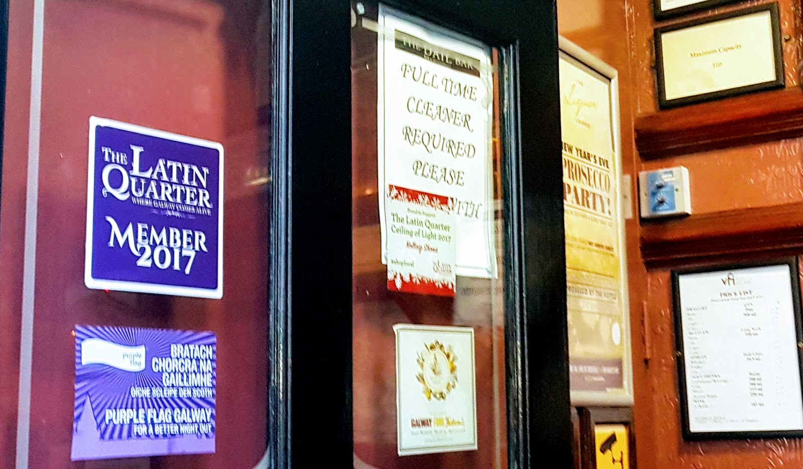 Job advert, alongside a sign for a new years eve prosecco party in the dial bar .  Also Latin Quarter 2017 member and purple flag safe city sticker