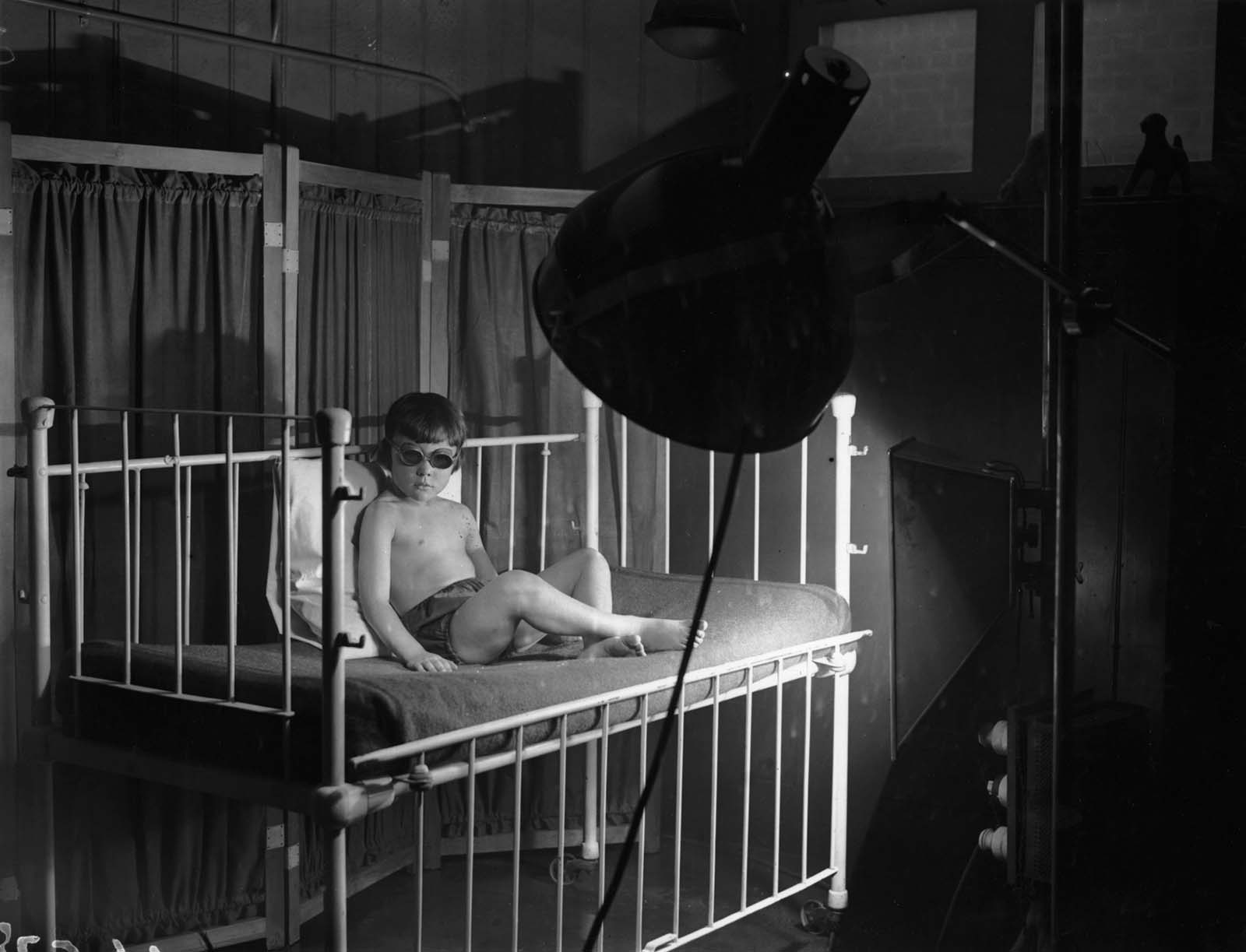 A child receiving treatment under an artificial sun lamp.
