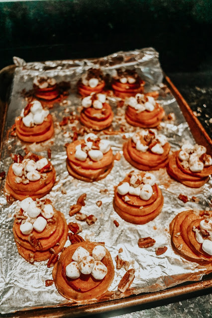 Baked sweet potato stacks topped with marshmallows, brown sugar, and pecans