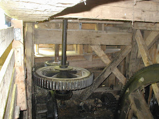 Gears inside the mill that transfer power from the water wheel outside to the grinding wheel