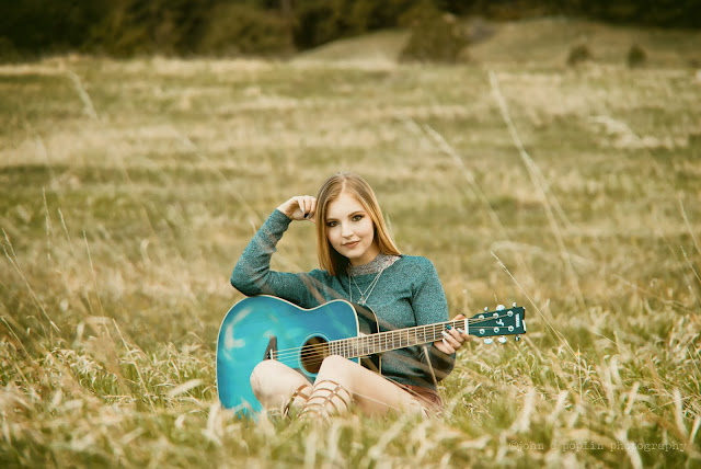 A young girl poses for senior portraits with a guitar in Boulder Colorado