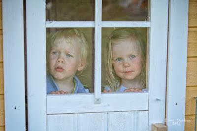 Saana ja Otso katselemassa leikkimökin oven ikkunoiden läpi