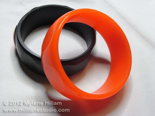 Orange and black resin bangles with flat spots