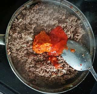 adding tomato sauce and hot sauce to the ground beef
