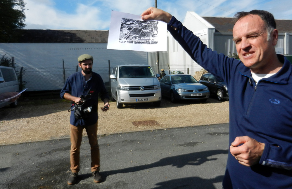 Man holds up aerial photo.
