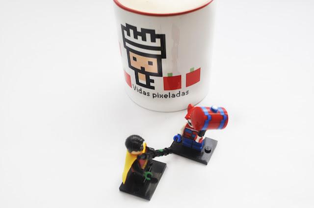 Robin y Harley de lego con sus armas tipicas un martillo y un palo bo, discuten delante de una taza de vidas pixeladas