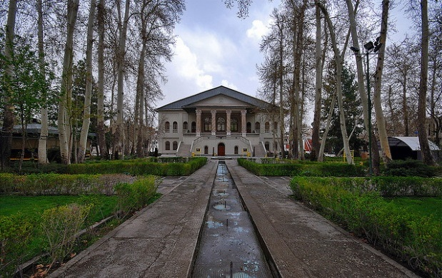 Very high trees in Ferdows Garden and the two story story mansion of Cinema Museum of Iran.