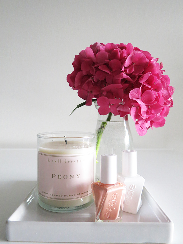 Essie Gel Couture nail polish and top coat with a pink hydrangea and a peony-scented candle