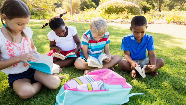 photo of kids reading outside on a sunny day