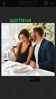 девушка и мужчина с щетиной сидят за столом
