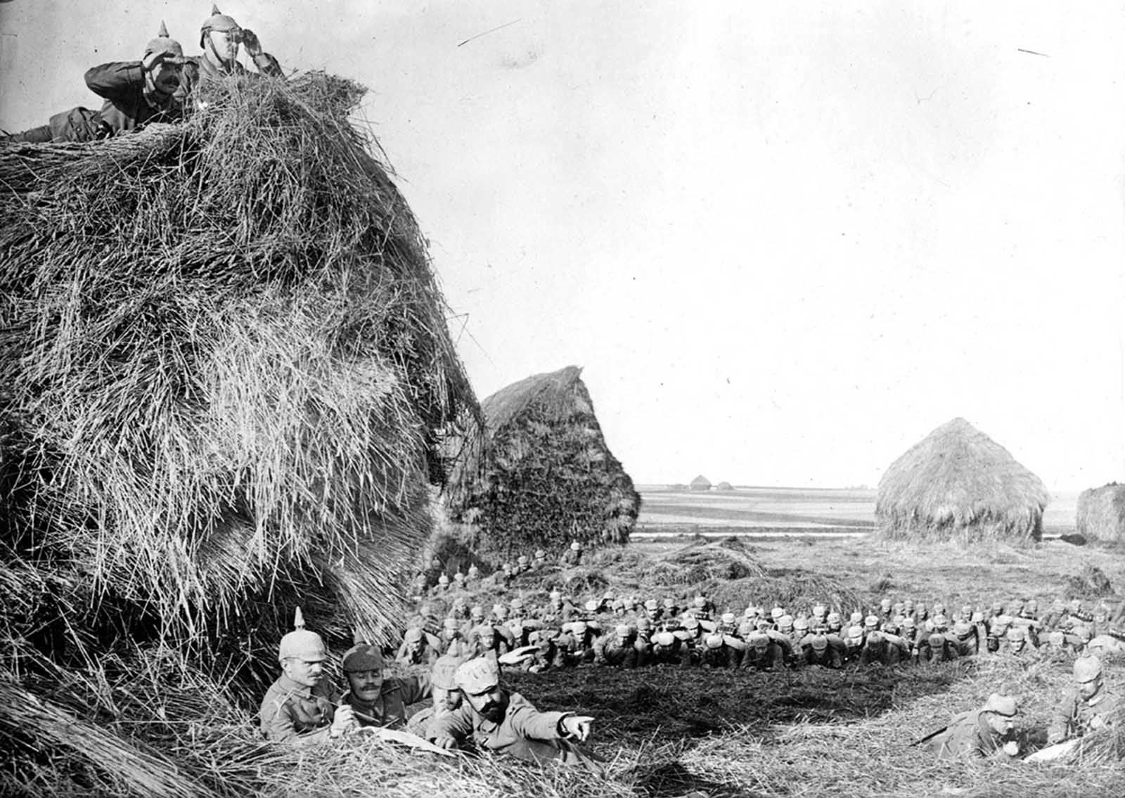 German soldiers make observations from atop, beneath, and behind large haystacks in southwest Belgium, ca. 1915.