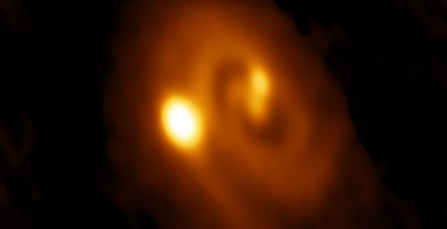 ALMA image of the L1448 IRS3B system, with two young stars at the center and a third distant from them. Spiral structure in the dusty disk surrounding them indicates instability in the disk, astronomers said. Credit: Bill Saxton, ALMA (ESO/NAOJ/NRAO), NRAO/AUI/NSF.