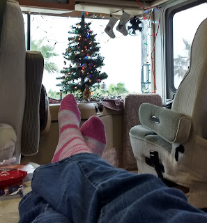 RV Christmas tree in background seem through sock covered feet resting on couch