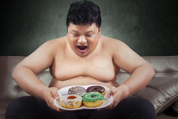 obese man looking at donuts