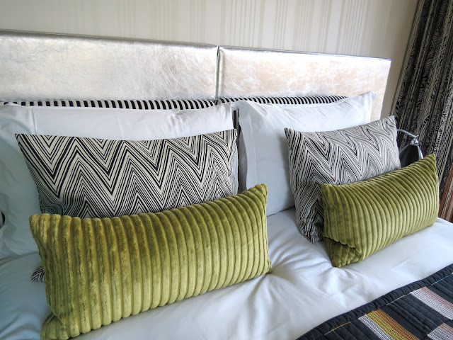 silver headboard bed green pillows and black