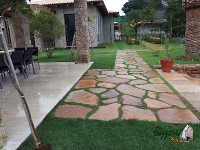 Execução do caminho no jardim com pedra Goiás tipo cacão com juntas de grama, dos revestimentos de pedra na fachada da residência em Piracaia-SP com execução do paisagismo e o gramado com grama esmeralda.