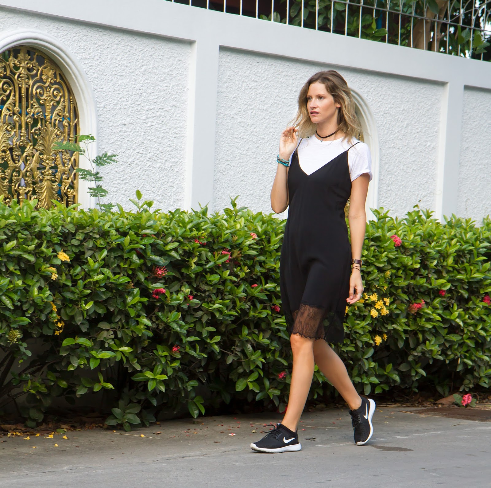 Fashion blogger, Alison Hutchinson, is wearing a white t-shirt under a black slip dress.