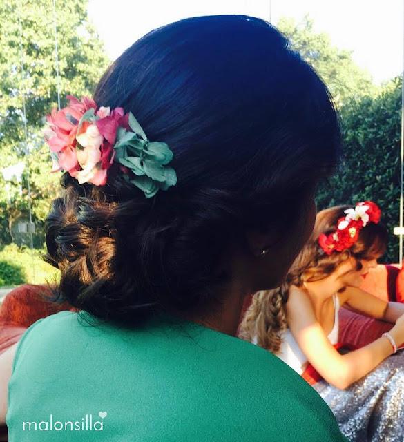 Invitada boda con tocado tipo peina en verde esmeralda y buganvilla en recogido bajo y vestido verde esmeralda