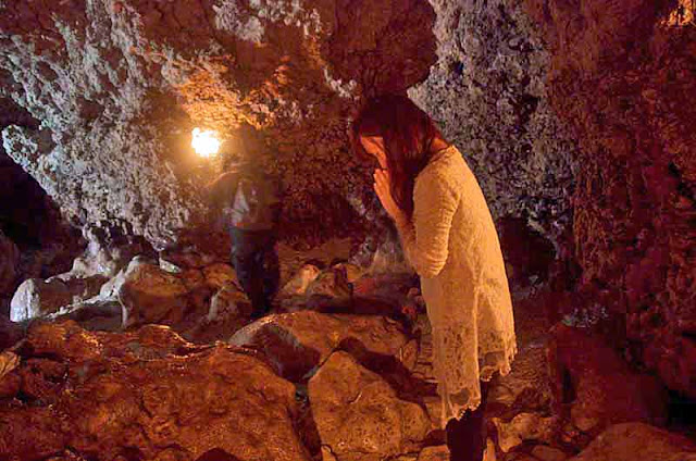 Woman in prayer at back entrance to cave facing water