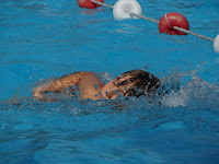 Image of child swimming in a swimming lane:-Teaching Kids To Swim with Quality Swimming Lesson Plans