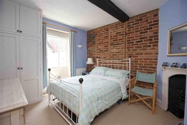 Iron bed against exposed brick wall